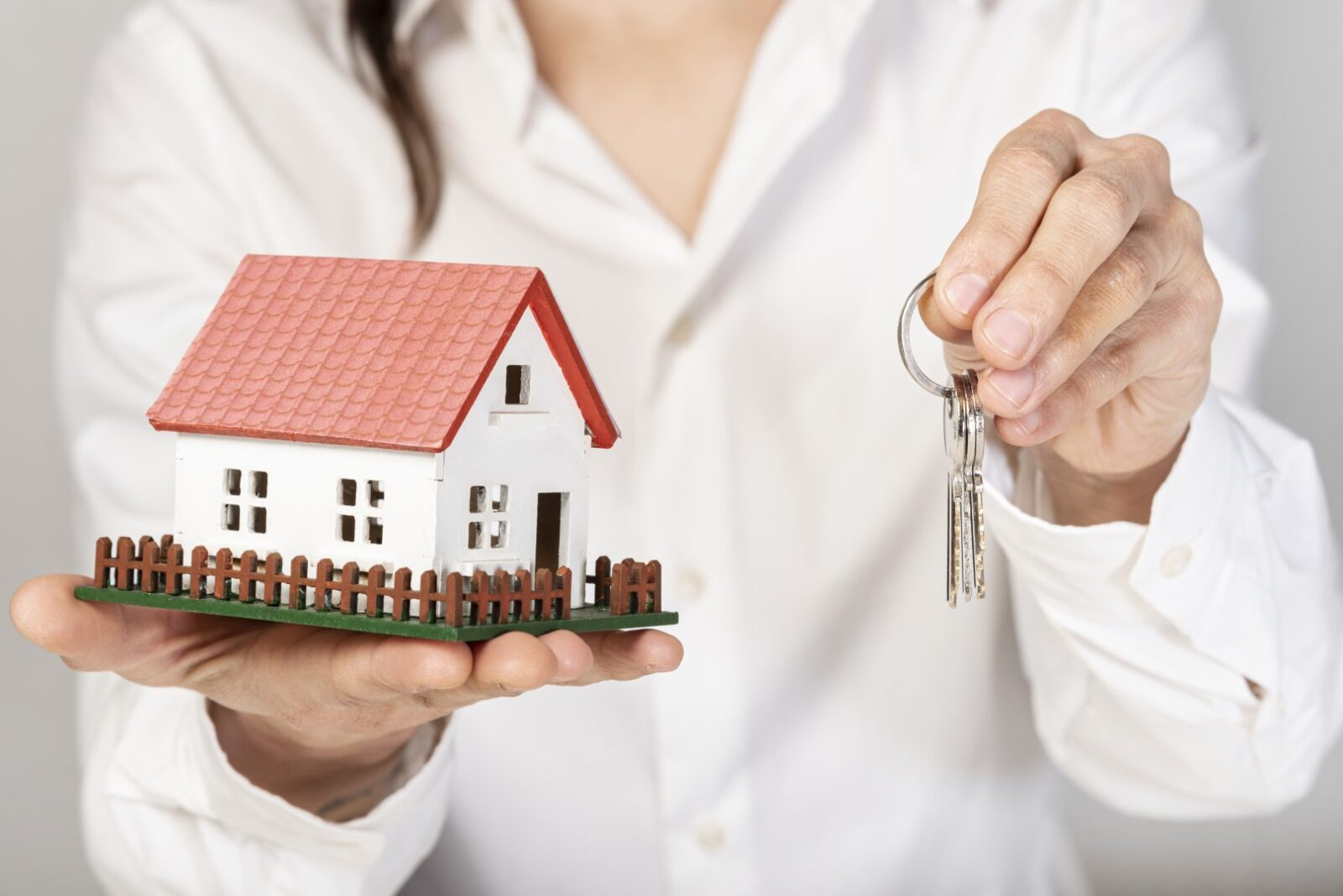 female-holding-a-toy-model-house-and-keys